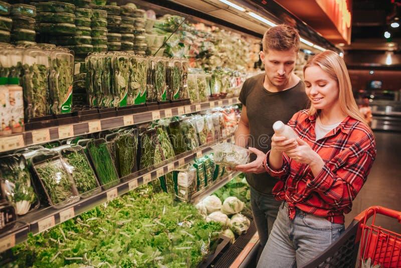 年轻夫妇在杂货店 他们站立在草本架子 她在手和微笑上拿着汁液bootle 她看它 人 库存图片