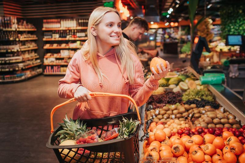 年轻夫妇在杂货店 在前面和举行篮子的妇女立场与橙色柿子 快乐的正面模型 人 免版税库存图片