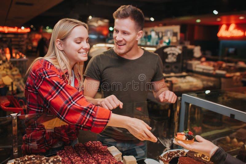 年轻夫妇在杂货店 宜人的年轻女人从手和微笑得到蛋糕 她到达手 年轻人看看她 图库摄影