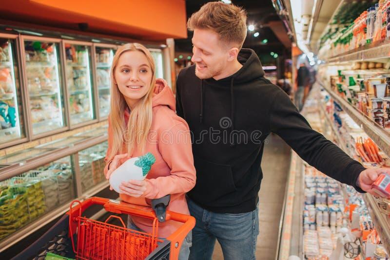年轻夫妇在杂货店 快乐的人购买食物 她举行牛奶瓶和微笑给人 她运载台车 免版税库存图片
