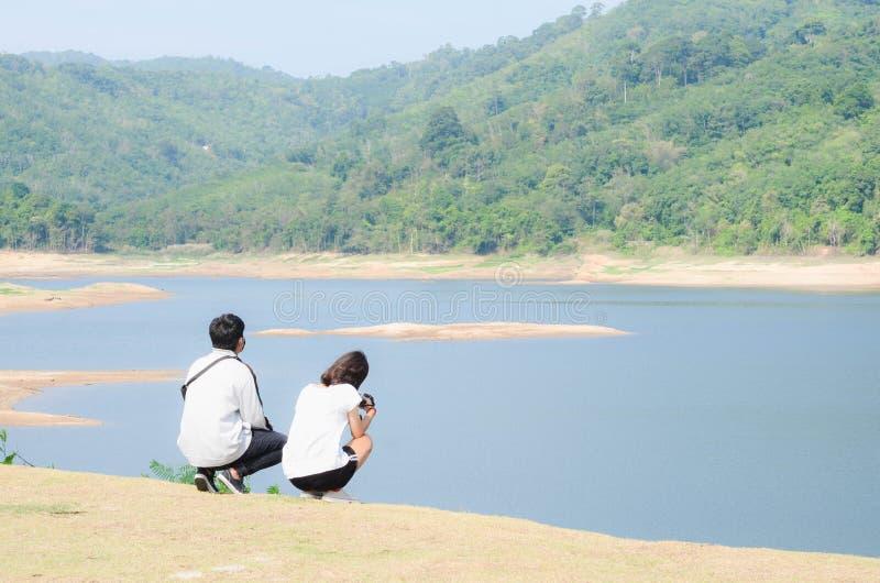 年轻夫妇在水坝旁边放松在跑步以后 免版税库存图片