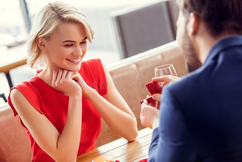 年轻夫妇在注视着快乐提案圆环的餐馆坐的妇女的日期 库存图片