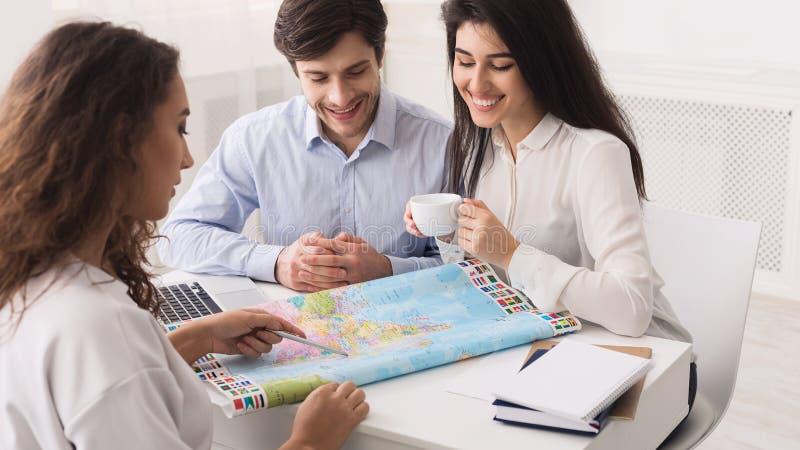 年轻夫妇在游览机构中,选择目的地 库存图片