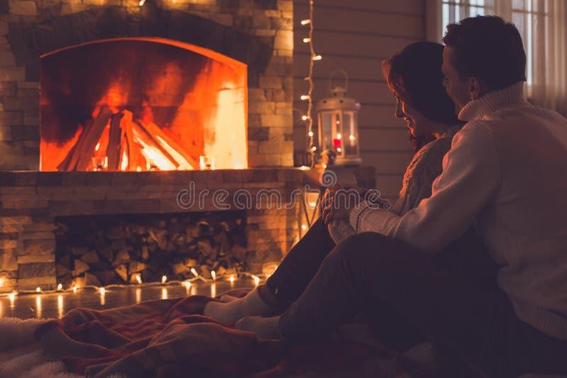 年轻夫妇在看火焰的壁炉在家冬天附近 免版税图库摄影