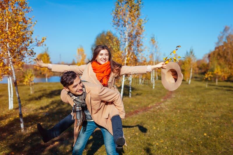年轻夫妇在秋天给他的女朋友肩扛的森林人走 有的乐趣人 库存图片