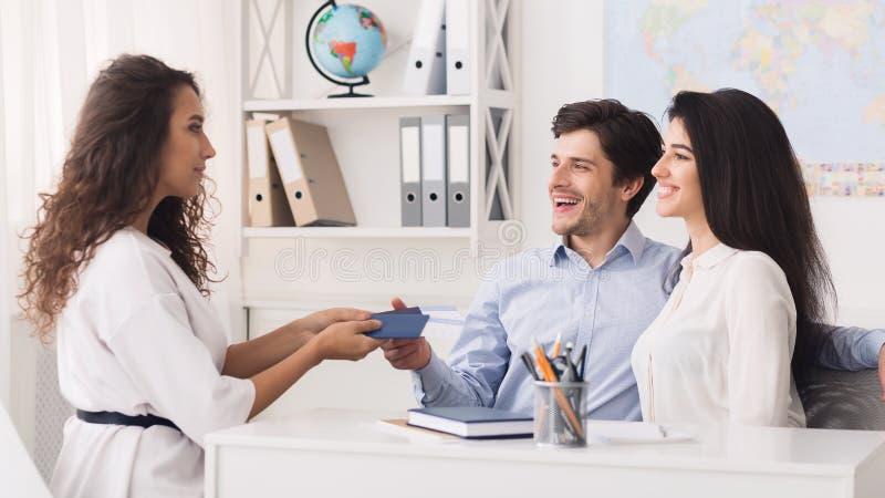 年轻夫妇在联络与旅行代理人的游览机构中 免版税库存照片