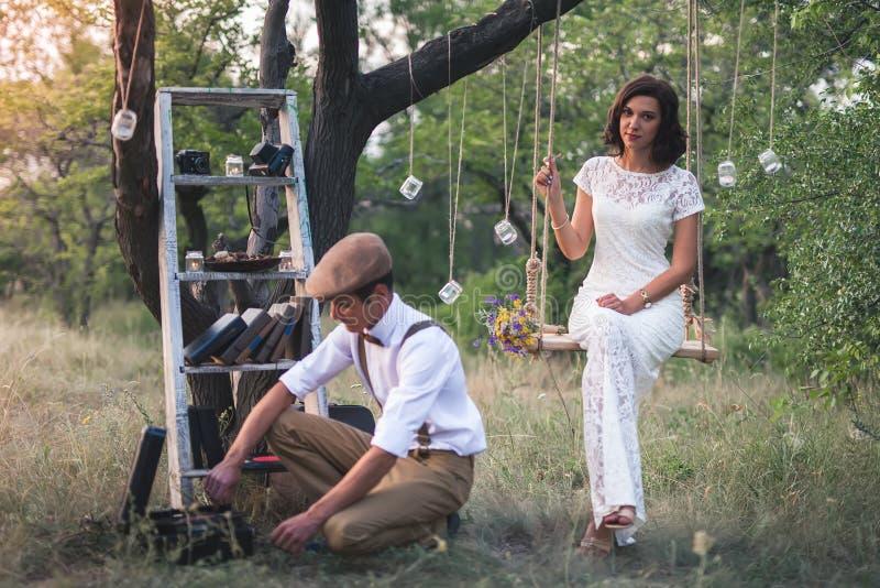 年轻夫妇在苹果树有他们的在土气样式的婚姻 库存照片
