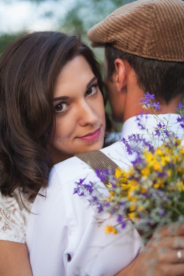 年轻夫妇在苹果树有在土气样式的婚姻 免版税库存照片