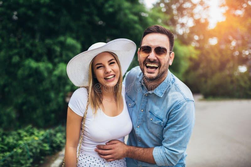 年轻夫妇在获得乐趣和一起享用在好日子的公园 免版税库存照片