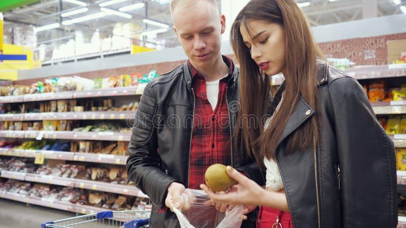 年轻夫妇在超级市场在塑料袋买梨,女孩投入梨 库存图片