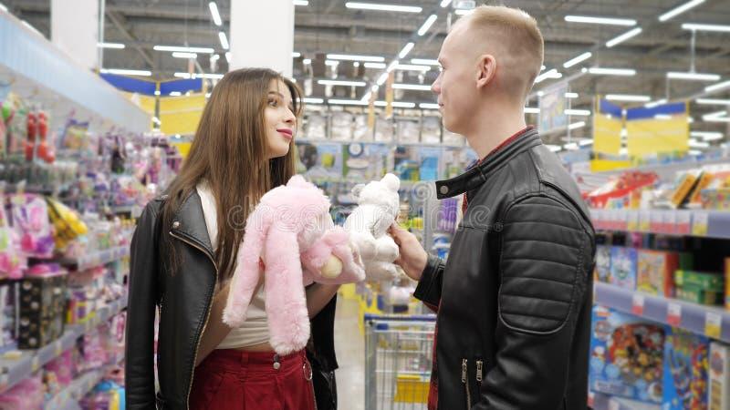 年轻夫妇在超级市场选择女用连杉衬裤玩具-桃红色女用连杉衬裤野兔或极性玩具熊 免版税库存图片