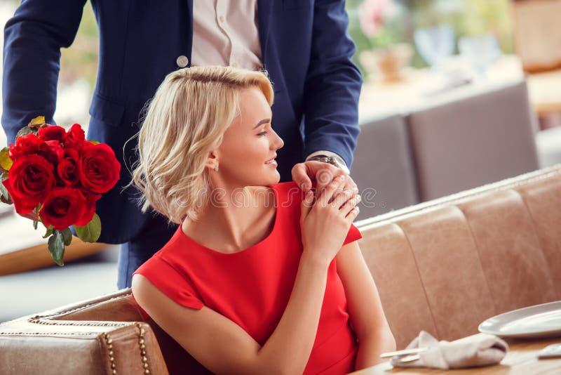 年轻夫妇在餐馆人身分的日期与在握他的手的坐的妇女后的花束快乐 免版税库存照片