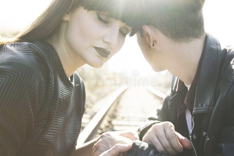 年轻夫妇坐一个被放弃的火车站的路轨 库存照片