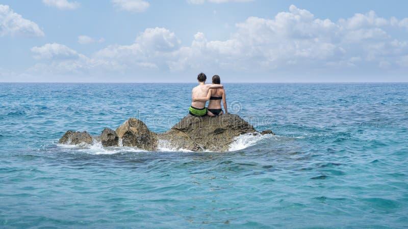 年轻夫妇坐峭壁 免版税图库摄影
