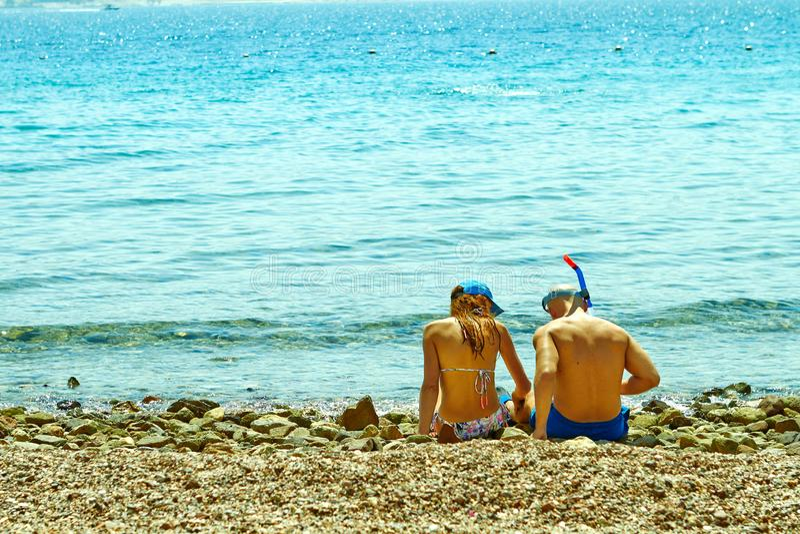年轻夫妇坐红海的岸 库存照片