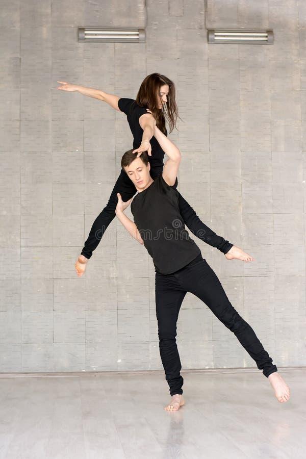 年轻夫妇实践杂技平衡 免版税库存照片