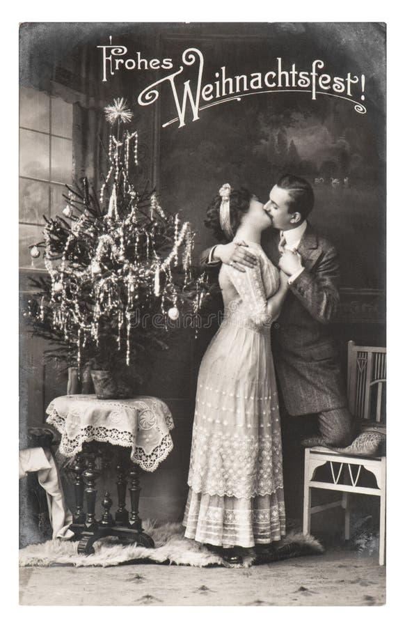 年轻夫妇庆祝了与圣诞树葡萄酒图片 免版税库存照片