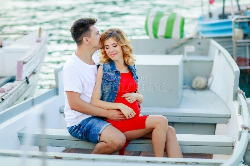 年轻夫妇拥抱和放松在小船附近的船坞,在晴朗的夏日 妇女和人时装的站立近 免版税图库摄影