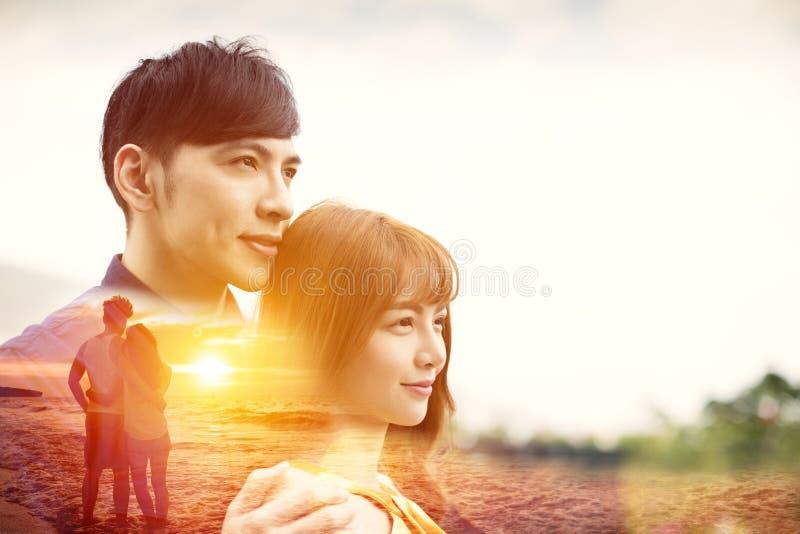 年轻夫妇拥抱的和观看的日落 免版税库存图片