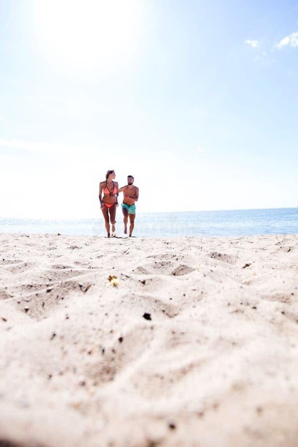 年轻夫妇是花费时间的乐趣在海洋上 免版税图库摄影