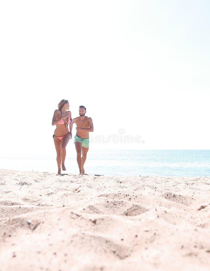 年轻夫妇是花费时间的乐趣在海洋上 库存照片