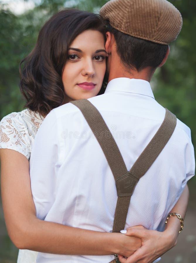 年轻夫妇有在土气样式的婚姻在领域 库存照片