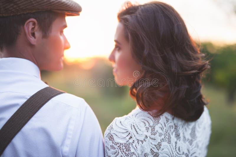 年轻夫妇有在土气样式的婚姻在领域 图库摄影