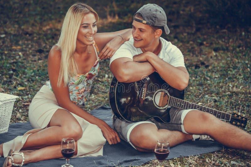 年轻夫妇有浪漫野餐在公园 库存照片