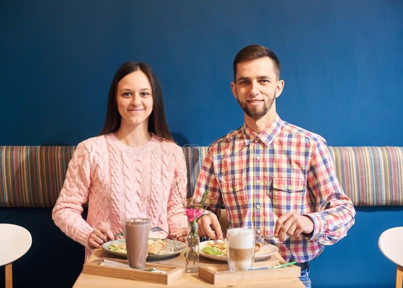 年轻夫妇朋友工友吃午餐在大气咖啡馆 在背景的蓝色装饰的墙壁 r 免版税库存照片