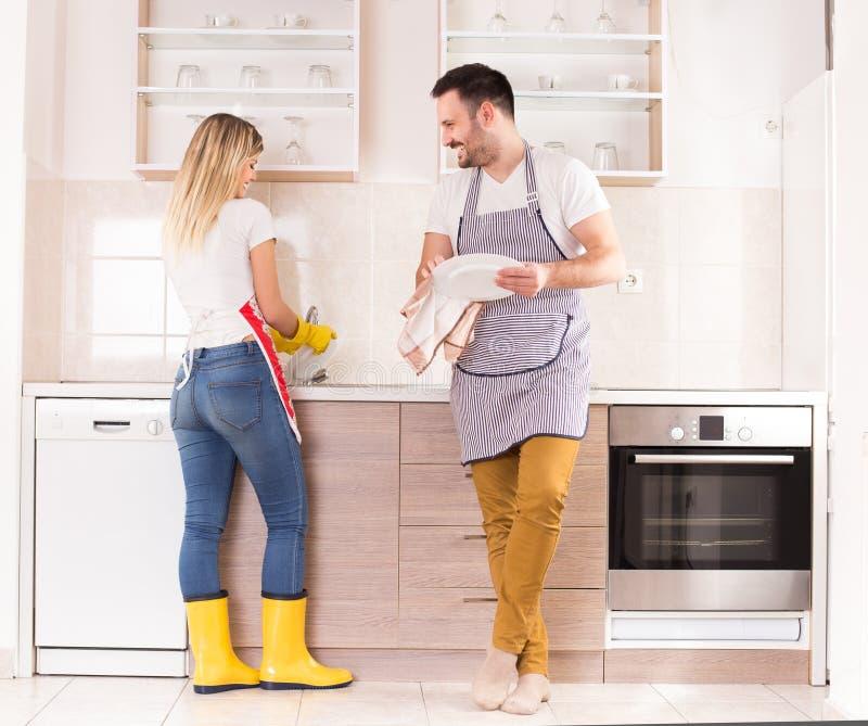 年轻夫妇洗涤的盘一起 库存图片