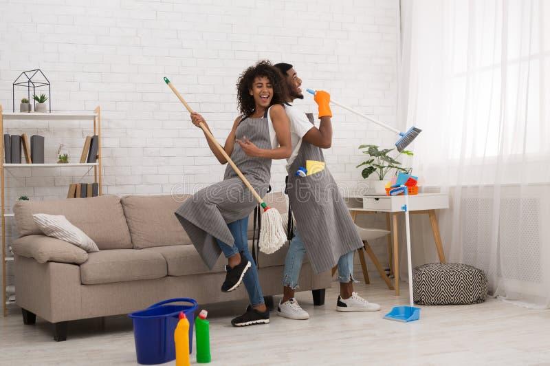 年轻夫妇清洁家,获得与拖把和笤帚的乐趣 免版税图库摄影