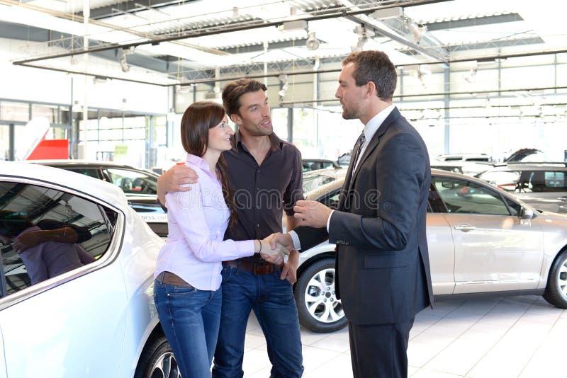 年轻夫妇由售车行的卖主劝告 免版税图库摄影