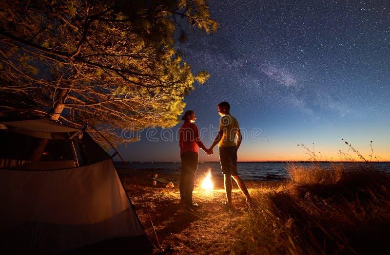 年轻夫妇男人和妇女有休息在旅游帐篷和灼烧的营火在海岸在森林附近 免版税库存图片