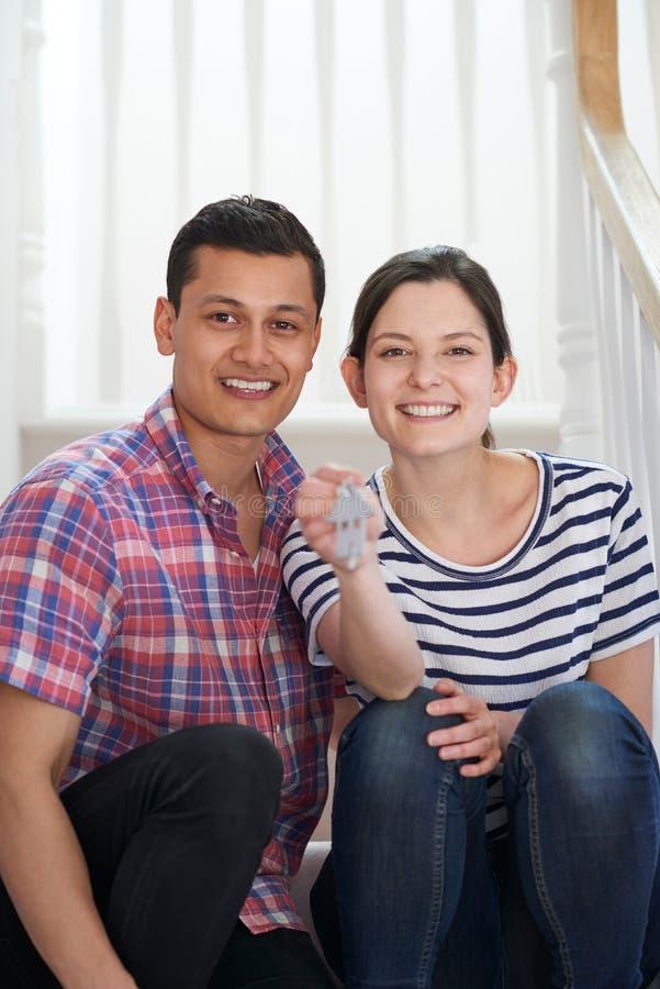 年轻夫妇画象坐把握关键的台阶对新的H 免版税库存图片