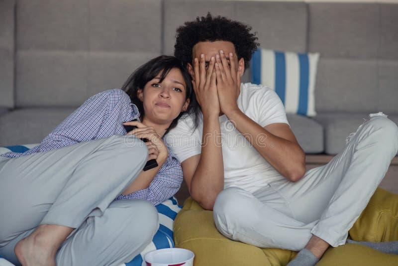 年轻夫妇画象坐观看与震惊表示的沙发一部电影在他们的面孔 图库摄影