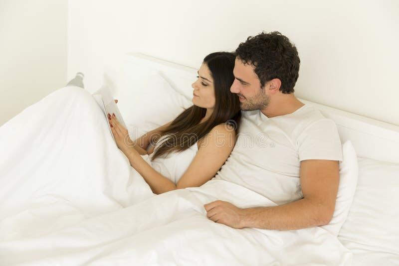 年轻夫妇看书在床上 免版税库存照片