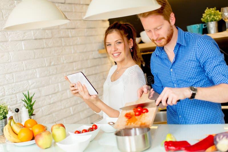 年轻夫妇获得乐趣在室内现代厨房,当准备v时 免版税库存照片