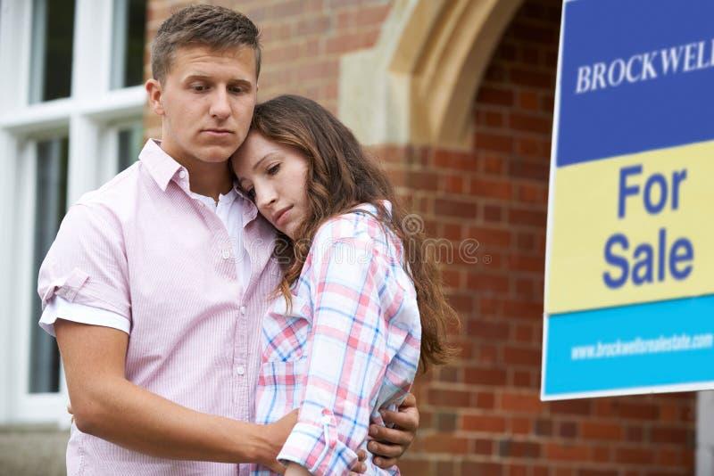年轻夫妇被迫通过站立户外在为销售标志旁边的经济卖在家 库存照片