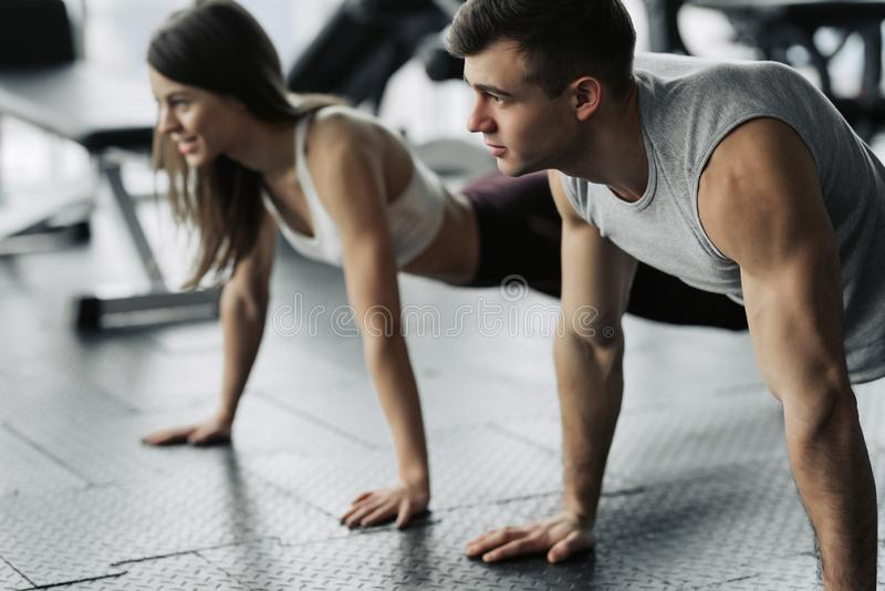 年轻夫妇解决在健身房 可爱的妇女和英俊的肌肉人在轻的现代健身房训练 做板条 推挤 免版税库存图片