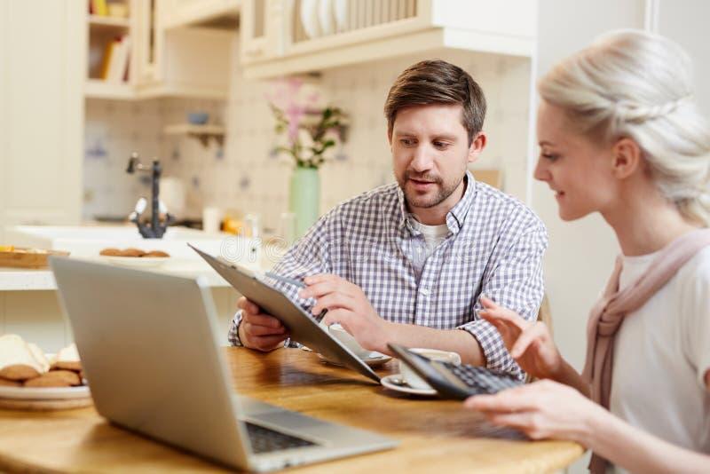 年轻夫妇谈论财务在厨房 免版税库存图片