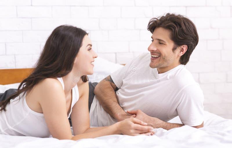 年轻夫妇谈话在卧室,互相听 库存图片