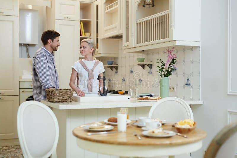 年轻夫妇谈话在国内厨房 库存照片