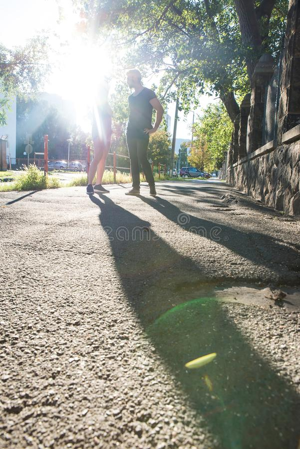 年轻夫妇谈话在日落在一个城市环境里 库存照片