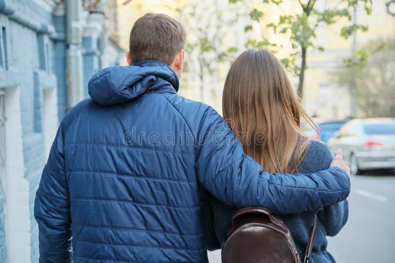 年轻夫妇走,可爱的男人和妇女,城市街道背景,后面视图春天室外画象  免版税库存照片