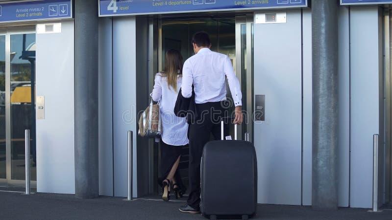 年轻夫妇输入的电梯在机场、商务旅行、旅行和旅游业 免版税库存图片