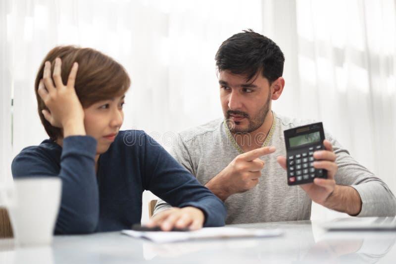 年轻夫妇辨证关于金钱在他们的房子 免版税库存图片
