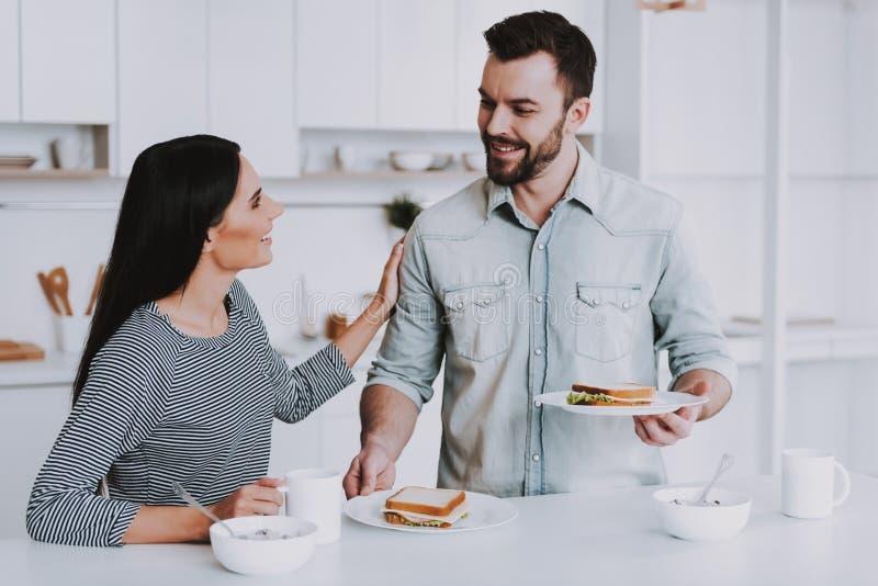 年轻夫妇食用早餐在现代厨房 库存图片