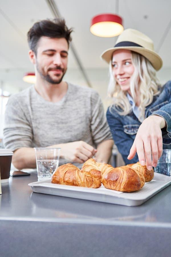 年轻夫妇饿并且吃新月形面包 库存照片