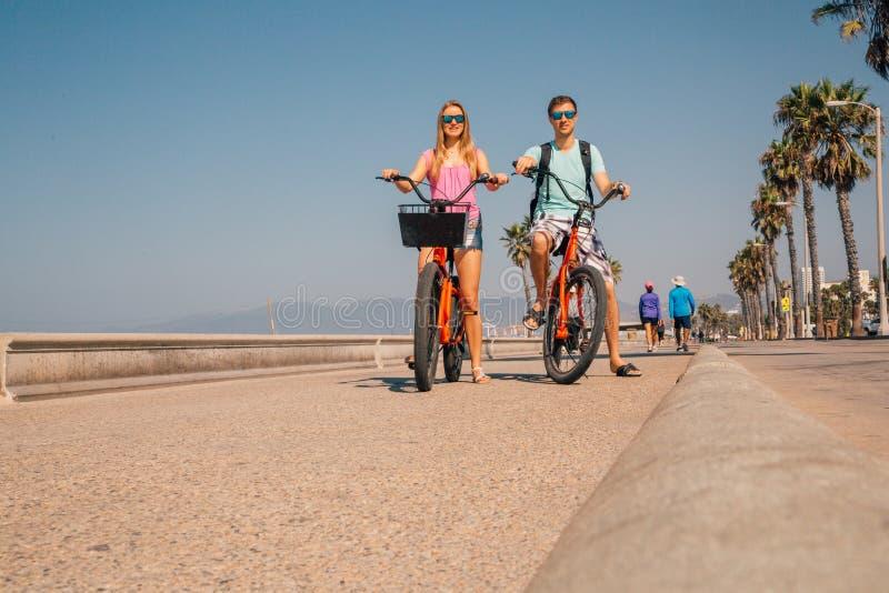年轻夫妇骑马骑自行车在威尼斯海滩下在洛杉矶 库存照片