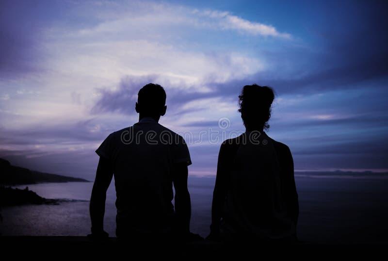 年轻夫妇` s剪影和风暴环境美化 免版税库存照片